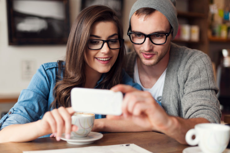 Hipster couple using mobile phone at cafe