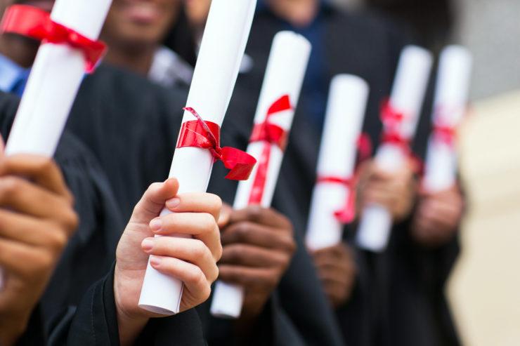group of graduates holding diploma